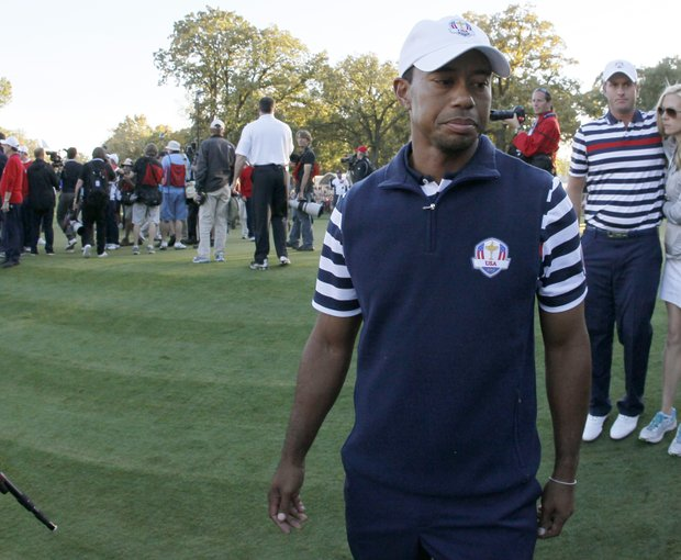 USA's Tiger Woods walks off the course as Europe celebrates their win at the Ryder Cup PGA golf tournament Sunday, Sept. 30, 2012, at the Medinah Country Club in Medinah, Ill.