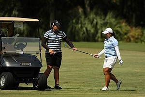 Moriya Jutanugarn hands her club to her sister Ariya during LPGA Qualifying School at LPGA International.