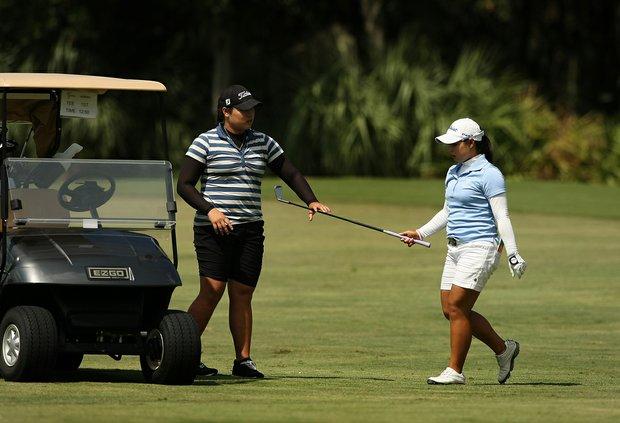Moriya Jutanugarn hands her club to her sister Ariya during LPGA Qualifying School at LPGA International.