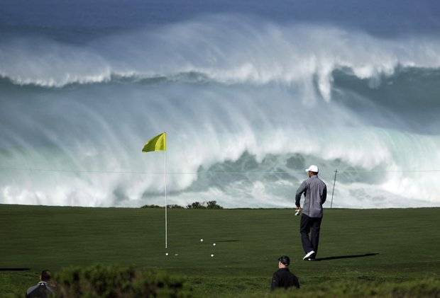Tiger Woods walks to his ball on the 15th green of the Monterey Peninsula Country Club shore course as waves crash in the background during a practice round at the AT&T Pebble Beach National Pro-Am PGA Tour golf tournament in Pebble Beach, Calif., Wednesday, Feb. 8, 2012.
