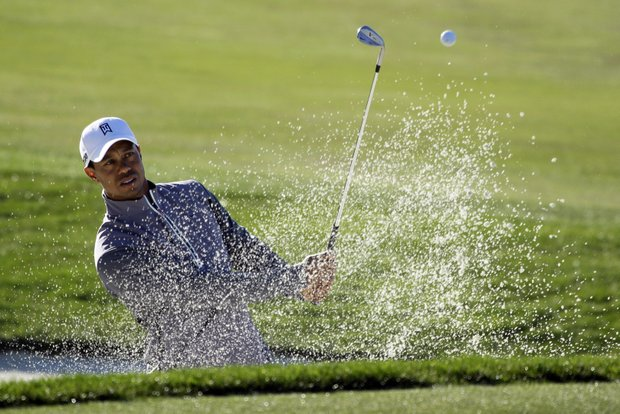 Tiger Woods hits his ball out of a bunker onto the sixth green of the Monterey Peninsula Country Club shore course during a practice round at the AT&T Pebble Beach National Pro-Am PGA Tour golf tournament in Pebble Beach, Calif., Wednesday, Feb. 8, 2012.