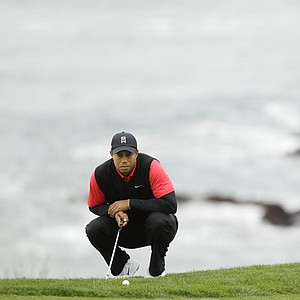 Tiger Woods kneels at the eighth green at Pebble Beach Golf Links during the final round of the AT&T Pebble Beach National Pro-Am golf tournament in Pebble Beach, Calif., Sunday, Feb. 12, 2012.