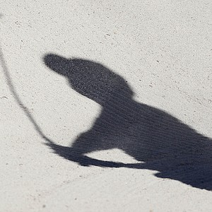 Tiger Woods casts a shadow as he hits out of a bunker on the 17th while playing Spain's Gonzalo Fernandez-Castano during the Match Play Championship golf tournament, Wednesday, Feb. 22, 2012, in Marana, Ariz.