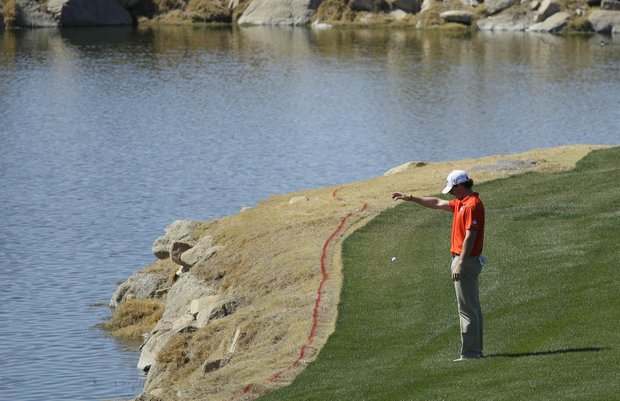 Northern Ireland's Rory McIlroy takes a drop on the third fairway after hitting into the water while playing South Korea's Sang-moon Bae during the Match Play Championship golf tournament, Saturday, Feb. 25, 2012, in Marana, Ariz.