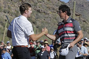 Hunter Mahan, left, shakes hands with Rory McIlroy after defeating him 2 and 1 to win the final round of the Match Play Championship golf tournament on Sunday, Feb. 26, 2012, in Marana, Ariz.