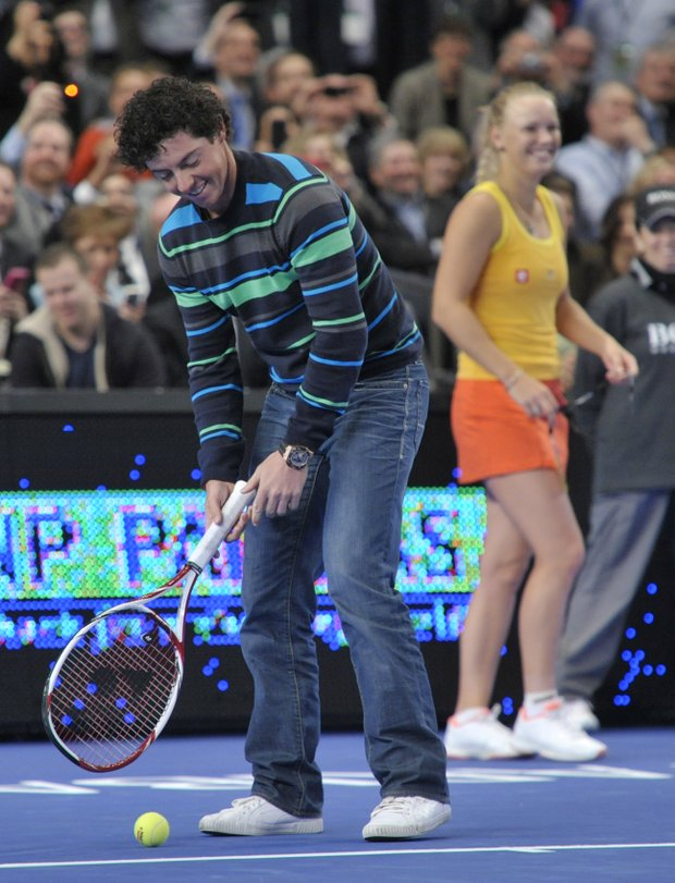 Golfer Rory Mcilroy, left, tees up a tennis ball to hit to Maria Sharapova as Caroline Wozniacki looks on in the BNP Paribas Showdown exhibition tennis match Monday, March 5, 2012, at Madison Square Garden in New York.