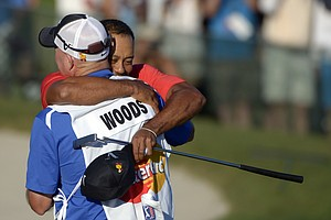 Tiger Woods, rear, embraces his caddie Joe LaCava after winning the Arnold Palmer Invitational golf tournament at Bay Hill in Orlando, Fla., Sunday, March 25, 2012.