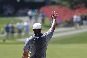 Tiger Woods accepts applause after hitting out of the sand along the 18th fairway during the Pro-Am round PGA play of the Wells Fargo Championship at Quail Hollow Club in Charlotte, N.C., Wednesday, May 2, 2012.