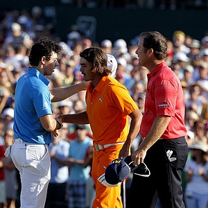 Rory McIlroy, of Northern Ireland, and Rickie Fowler, center, hug on the 18th green following a playoff during the final round of the Wells Fargo Championship golf tournament at Quail Hollow Club in Charlotte, N.C., Sunday, May 6, 2012. At right is D.A. Points, who also was in the playoff. Fowler won the tournament.