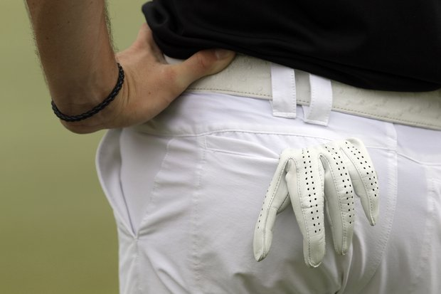 The golf glove of Rory McIlroy, of Northern Ireland, hangs out of his pocket as he waits to putt on the ninth green during the final round of the St. Jude Classic golf tournament on Sunday, June 10, 2012, in Memphis, Tenn.