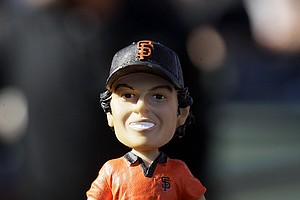 A member of the media holds a bobblehead of golfer Rory McIlroy before a baseball game between the San Francisco Giants and the Houston Astros in San Francisco, Tuesday, June 12, 2012. McIlroy was scheduled to throw out the ceremonial first pitch. The bobbleheads were given out to fans.