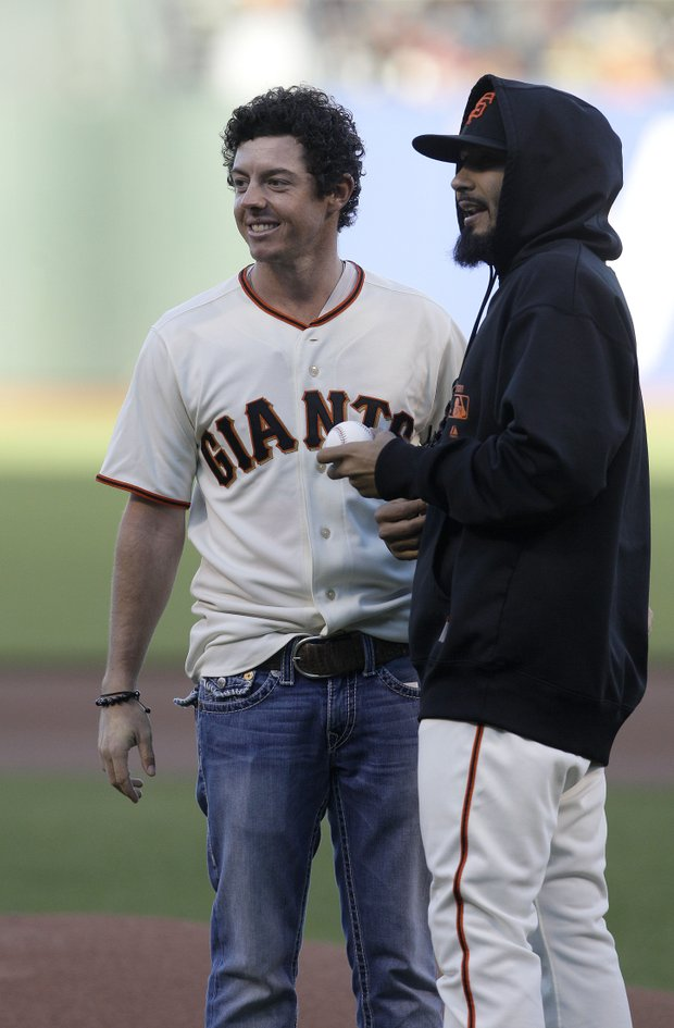 Golfer Rory McIlroy, of Northern Ireland, left, and San Francisco Giants pitcher Sergio Romo (54) after the ceremonial first pitch before of a baseball game between the San Francisco Giants and the Houston Astros in San Francisco, Tuesday, June 12, 2012.