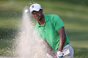 Tiger Woods hits out of a bunker onto the 14th green during the third round of the AT&T National golf tournament at Congressional Country Club in Bethesda, Md., Saturday, June 30, 2012.