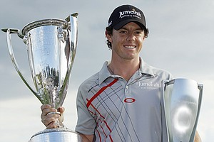 Rory McIlroy, of Northern Ireland, holds the Western Golf Association's J.K. Wadley trophy, left, and the BMW trophy after winning the BMW Championship PGA golf tournament at Crooked Stick Golf Club in Carmel, Ind., Sunday, Sept. 9, 2012.