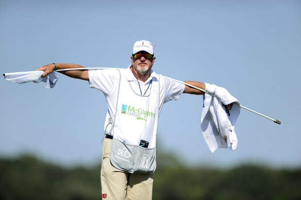 Zach Johnson's caddie Damon Green holds flag on the 15th green the during the third round of the McGladrey Classic PGA Tour golf tournament Saturday, Oct. 20, 2012 in St. Simons Island, Ga.