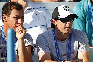 Golfer Rory McIlroy, right, watches Caroline Wozniacki, from Denmark, play a match against Sesil Karatantcheva, from Kazakhstan, at the Western & Southern Open tennis tournament, Wednesday, Aug. 15, 2012, in Mason, Ohio.