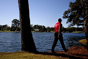 Tiger Woods walks toward the fairway after teeing off on the 17th hole during the final round of the Tour Championship golf tournament Sunday, Sept. 23, 2012, in Atlanta.