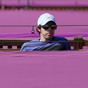Golfer Rory McIlroy, of Northern Ireland, watches his girlfriend, tennis player Caroline Wozniacki, practice at the All England Lawn Tennis Club at Wimbledon, London, at the 2012 Summer Olympics, Wednesday, July 25, 2012. Tennis competition is scheduled to begin Saturday, July 28.