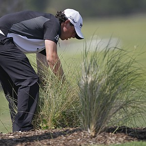 Rory McIlroy of Northern Ireland looks for his ball in the weeds on the third hole during the third round of the PGA Championship golf tournament on the Ocean Course of the Kiawah Island Golf Resort in Kiawah Island, S.C., Saturday, Aug. 11, 2012.