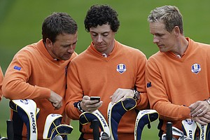 Europe's Graeme McDowell, left, and Luke Donald look at Rory McIlroy's phone during their team photo at the Ryder Cup PGA golf tournament Tuesday, Sept. 25, 2012, at the Medinah Country Club in Medinah, Ill.
