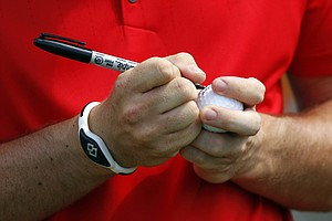 Rory McIlroy, of Northern Ireland, autographs a ball on the seventh tee during the final round of the PGA Championship golf tournament on the Ocean Course of the Kiawah Island Golf Resort in Kiawah Island, S.C., Sunday, Aug. 12, 2012.