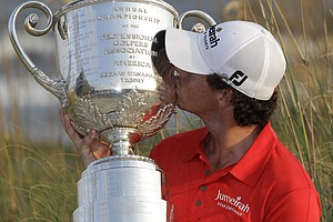 Rory McIlroy of Northern Ireland kisses the championships trophy for photographers after the final round of the PGA Championship golf tournament on the Ocean Course of the Kiawah Island Golf Resort in Kiawah Island, S.C., Sunday, Aug. 12, 2012.