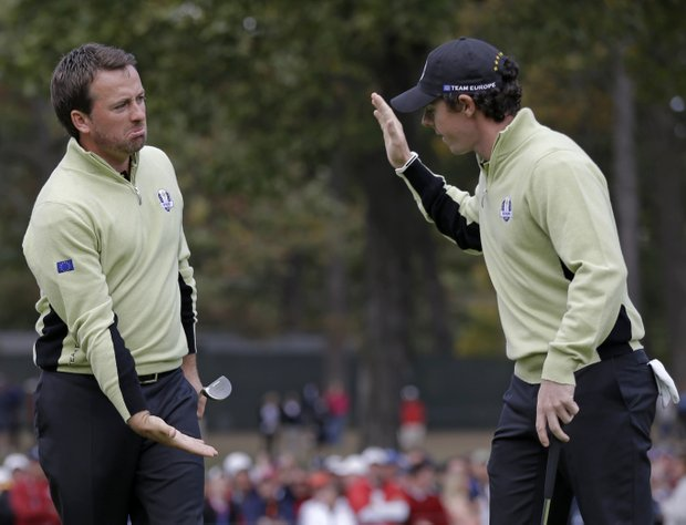 Europe's Graeme McDowell, left, is congratulated by Rory McIlroy after making a putt to half the 13th hole during a foursomes match at the Ryder Cup PGA golf tournament Friday, Sept. 28, 2012, at the Medinah Country Club in Medinah, Ill.