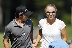 Rory McIlroy, left, walks onto the first green with his girlfriend Caroline Wozniacki during the Pro Am round of the Deutsche Bank Championship golf tournament at TPC Boston in Norton, Mass., Thursday, Aug. 30, 2012.