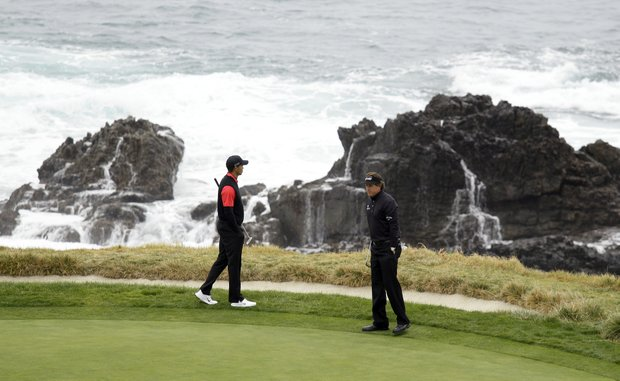 Tiger Woods, left, and Phil Mickelson stand on the seventh green at Pebble Beach Golf Links during the final round of the AT&T Pebble Beach National Pro-Am golf tournament in Pebble Beach, Calif., Sunday, Feb. 12, 2012.