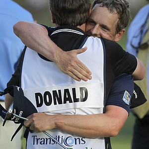 Luke Donald, right, hugs his caddie, John McLaren, after winning the Transitions Championship golf tournament in a playoff Sunday, March 18, 2012, in Palm Harbor, Fla.