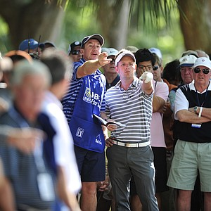 Luke Donald, of England, and his caddy John McLaren looks for a way out of the trees on the 15th fairway during the second round of the RBC Heritage golf tournament in Hilton Head Island, S.C., Friday, April 13, 2012.