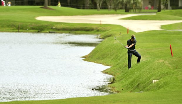 Luke Donald, of England, hits his ball near the water hazard on the fifth fairway during the final round of the RBC Heritage golf tournament in Hilton Head Island, S.C., Sunday, April 15, 2012.