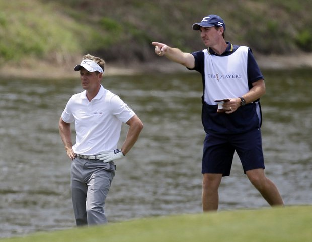 Luke Donald, left, of England, gets help from his caddie, John McLaren, on the fifth fairway during the third round of the Players Championship golf tournament at TPC Sawgrass, Saturday, May 12, 2012, in Ponte Vedra Beach, Fla.