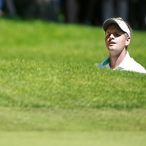 England's Luke Donald looks to play from a bunker on the 1st hole during the third round of the PGA Championship at the Wentworth golf club, Virginia Water, England, Saturday May 26, 2012.