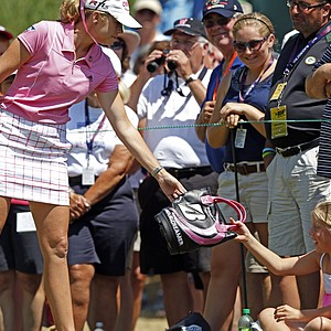 Paula Creamer hands a small girl a bag before she hits her tee shot on the first hole during the final round of the U.S. Women's Open golf tournament, Sunday, July 8, 2012, in Kohler, Wis.