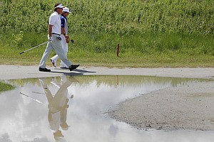 Phil Mickelson, foreground, and Rickie Fowler walks past a puddle during a stormy practice round for the PGA Championship golf tournament on the Ocean Course of the Kiawah Island Golf Club in Kiawah Island, S.C., Tuesday, Aug. 7, 2012.