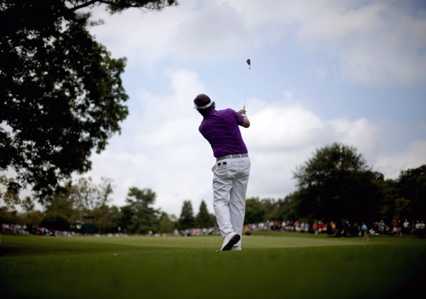 Phil Mickelson hits off the fairway on the first hole during the first round of the Tour Championship golf tournament Thursday, Sept. 20, 2012, in Atlanta.