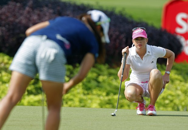 Paula Creamer, right, of the United States lines up her putt on the 2nd green during the final round of the LPGA Malaysia golf tournament at Kuala Lumpur Golf and Country Club in Kuala Lumpur, Malaysia, Sunday, Oct. 14, 2012.