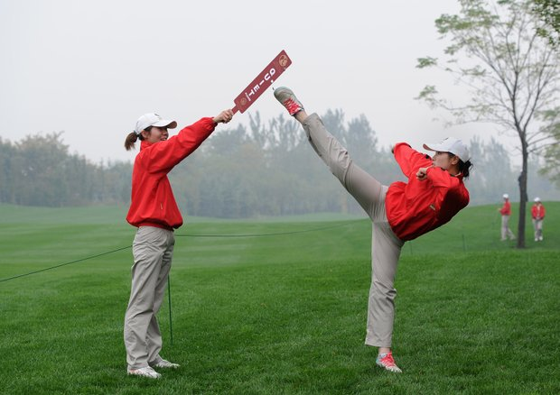 A course marshall practices some moves prior to the tee off time of World No. 1 Rory McIlroy and World No. 2 Tiger Woods for the 'Duel at Jinsha Lake', a one-day golf exhibition.