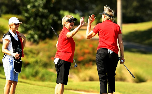 Jane Crafter of Australia, center, high-fives her playing partner Sally Little of South Africa during the ISPS Handa Cup at Reunion Resort. Crafter had one win on the LPGA and Little had 15.