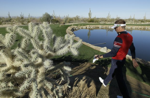 England's Ian Poulter walks by a jumping cholla cactus on his way to the fourth tee during the Match Play Championship golf tournament, Wednesday, Feb. 22, 2012, in Marana, Ariz.