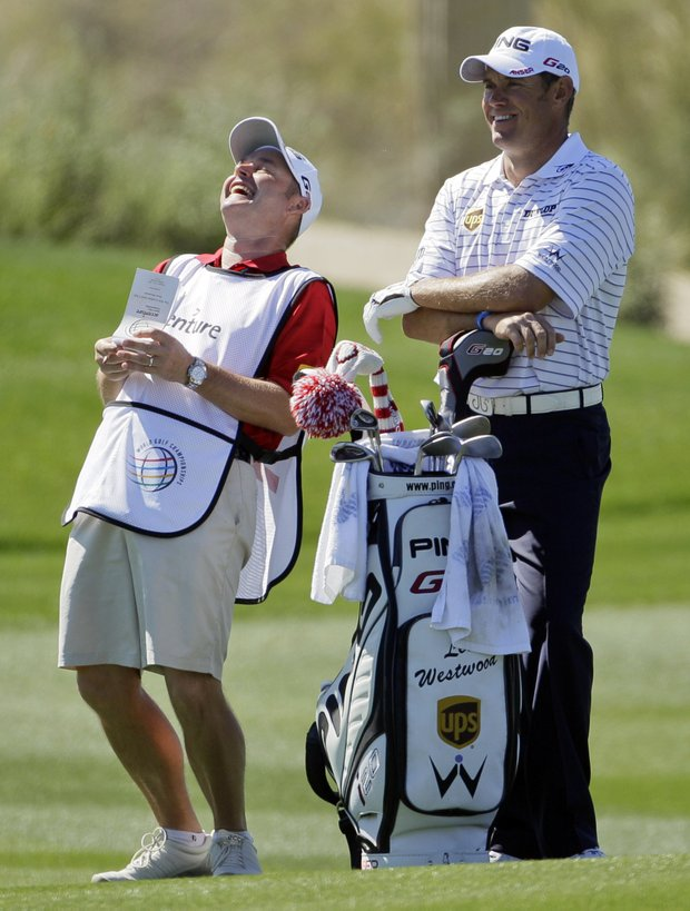 Lee Westwood, right, laughs with his caddie while waiting to take his shot on the seventh fairway against Nick Watney during the Match Play Championship golf tournament on Friday, Feb. 24, 2012, in Marana, Ariz.