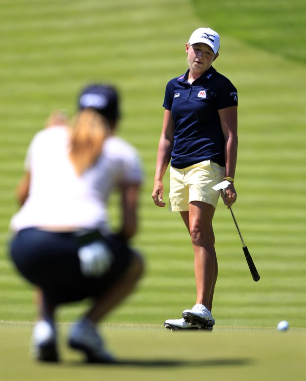 As Azahara Munoz, left, of Spain, looks on, Stacy Lewis reacts to a missed putt on the first hole during their fourth-round match in the LPGA Sybase Match Play Championship golf competition at Hamilton Farm Golf Club in Gladstone, N.J., Saturday, May 19, 2012.