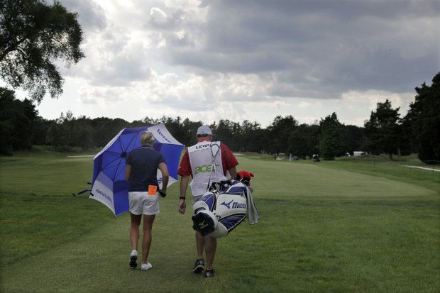 Stacy Lewis holds an umbrella against the wind and walks with her caddie Travis Wilson in a brief rain squall along the fairway of the 13th hole during the final round of the LPGA ShopRite Classic golf competition at Stockton Seaview Hotel and Golf Club in Galloway Township, N.J., Sunday, June 3, 2012. Lewis won the tournament.
