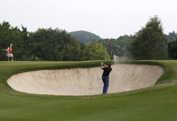 Ian Poulter from England hits a bunker shot at the 17th hole during the third round of the HSBC Champions golf tournament in Dongguan, southern China's Guangdong province, Saturday Nov. 3, 2012.