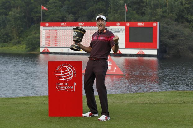 Ian Poulter from England holds a trophy as he poses for the photographers after winning the HSBC Champions golf tournament in Dongguan, southern China's Guangdong province, Sunday Nov. 4, 2012.