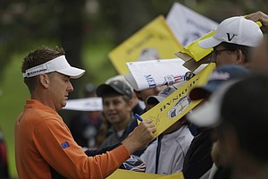 Europe's Ian Poulter signs autographs during the Ryder Cup PGA golf tournament Tuesday, Sept. 25, 2012, at the Medinah Country Club in Medinah, Ill.