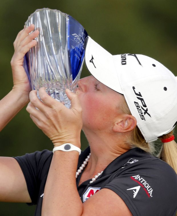 Stacy Lewis of the United States kisses the trophy for photographers after winning the Mizuno Classic golf tournament at Kintetsu Kashikojima Country Club in Shima, central Japan, Sunday, Nov. 4, 2012.