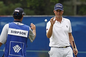 Defending champion Webb Simpson, right, catches a ball tossed by his caddie on the first hole during the Pro-Am for the Wyndham Championship golf tournament in Greensboro, N.C., Wednesday, Aug. 15, 2012.