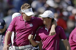 Europe's Ian Poulter and Rory McIlroy talk as they walk up the first hole during a four-ball match at the Ryder Cup PGA golf tournament Saturday, Sept. 29, 2012, at the Medinah Country Club in Medinah, Ill.